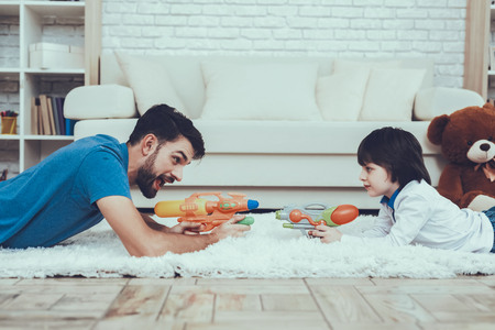 Plays Games. Happy Together. Boy. Have Fun. Son. Smiling Kid. Father. Leisure Time. Man. Smile. Home Time. Toys. Teddy Bear. Cars. Holidays. Spends Time. Have a Good Time. Happiness.