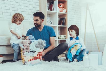 Dos chicos. Ayuda a lavar la ropa. Padre. Bebé con cabello brillante. Niños sonrientes. Pasa el tiempo. Felices juntos. Ocio. Hombre. Sonrisa. Hora de casa. Familia. Días festivos. Padre dos niños. Ropa sucia. Cesta. Foto de archivo