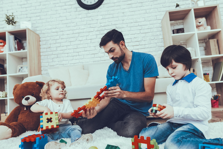 Plays Games. Toys. Teddy Bear. Cars. Holidays. Spends Time. Happy Together. Leisure Time. Smiling Kids. Father. Father Two Boys. Man. Smile. Home Time. Baby with Bright Hair. Two Boys.