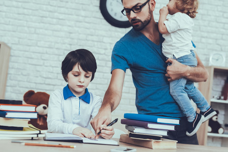 Difficulties Tasks.Dad. Helps do Homework. Spends Time with Son. Father. Father Two Boys. Upbringing. Looks After. Home Time.Boy. Sit at Homework. Textbook. Exercise Book. Study. Tired Kid. Notebook. Stok Fotoğraf