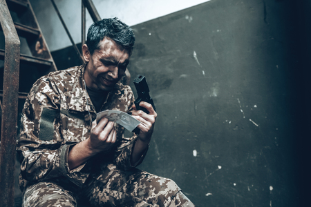 Man Is Sitting In War Shelter With Shotgun.   Depressed Soldier. Disappointed Hero. Banque d'images