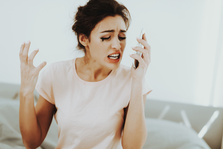 Crying Lonely Woman Phone Call. Bedroom Concept. Flowed Mascara. Unhappy Holiday. Sad Weekend. Tears On The Face. Sunny Day. Disappointed Girl. Spoiled Makeup. Female In A Bad Mood.