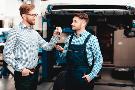 Car Owner Gives Keys To The Auto Mechanic In Garage. Trust Showing. Professional Uniform. Confident Engineer Stare. Repair Young Specialist. Service Station Concept. Machine Repairing. Stock Photo