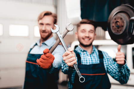 Two Automechanics Posing With Wrenches In Garage. Professional Uniform. Service Station Concept. Confident Engineer Stare. Detail Repairing. Under The Vehicle. Automobile Diagnostic. 写真素材 - 109389615