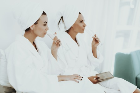 Smiling Girls In A Bathrobes Are Drinking Champagne. Beautiful Shiny Smile. Sunny Day. Good Mood. Young And Attractive. Towel On Head. Good Mood. Tablet Screen. Pre-wedding Care Concept.