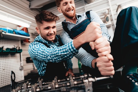 Two Auto Mechanics Work Together In Garage. Wrench Using. With All Might. Information Sharing. Professional Uniform. Confident Engineering Specialist Team. Service Station Concept. Stock Photo