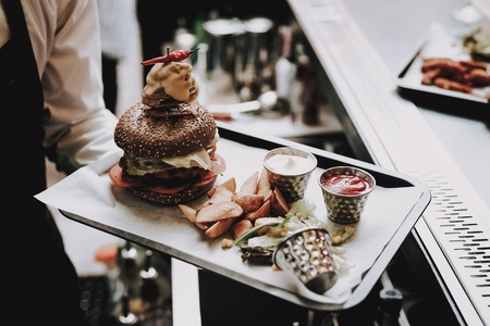 Burger. Barman. Food to Customers. Group of Young People. Rest. Bar. Have Fun. Barman with Beard. Together. Joyful. Chin-chin. Leisure Time. Nightlife. Positive. Emotion. Clubbing. Guys.