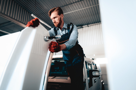 Red-haired Mechanic Is Looking Under The Hood. Professional Uniform. Confident Engineering Specialist Stare. Protective Gloves. Working In The Garage. Young Repairman Posing Concept. Big SUV.