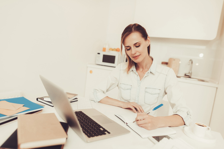 Young Woman Is Making Notes At The Kitchen. Work From Home With A Laptop Concept. Problems Solving. Official Clothes. Comfortable Environment. Calmness And Confidence. Concentrated Worker. Stockfoto