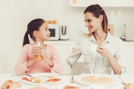 Mom With Daughter Are Having A Dinner At Kitchen. Family Relationship Concept. Having Fun During The Breakfast. Morning Nutrition. Juice Drinking. Happy Childhood Concept. Time To Lunch. Foto de archivo - 109389668