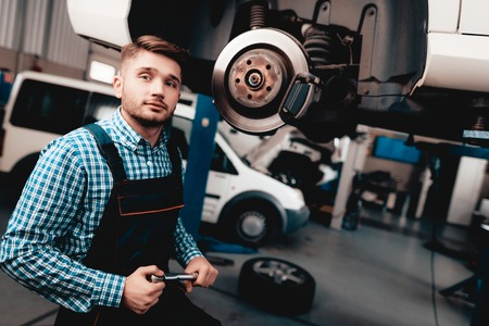 Young Auto Mechanic Repairs Automotive Hub In Garage. Professional Uniform. Service Station Concept. Confident Engineer Stare. Detail Repairing. Under The Vehicle. Automobile Diagnostic.