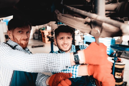 Young Mechanic Repairs Automotive Hub In Garage. Professional Uniform. Service Station Concept. Confident Engineer Stare. Detail Repairing. Under The Vehicle. Automobile Diagnostic. Join Forces. 版權商用圖片
