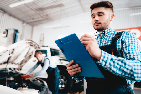 Young Mechanic Posing In Garage With Tablet Desk. Service Station Concept. Working Together In The Garage. Car Reparing With Wrench. Notes Making. Team Work. Automobile Diagnostic.