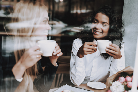 Food to Customers. Blond Girl. Mulatto. Sit. Cafe. Drink Coffee. Window. Have Fun. Food in Plate. Rest. Together. Joyful. Chin-chin. Leisure Time. Nightlife. Positive. Emotion. Clubbing. Guys. Stock Photo