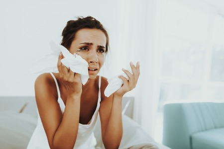 Sad Woman With Flowed Mascara Wipes The Tears. With Paper Napkin. Unhappy Holiday. Sad Weekend. Tears On The Face. Disappointed Girl. Female In The Bad Mood. Alone In The Bedroom.
