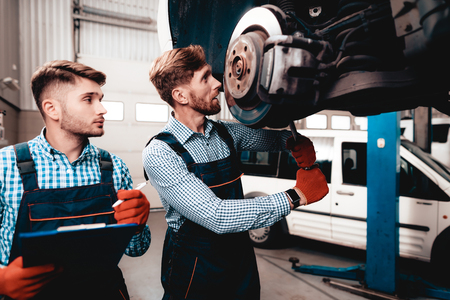 Young Mechanic Repairs Automotive Hub In Garage. Professional Uniform. Service Station Concept. Confident Engineer Stare. Detail Repairing. Under The Vehicle. Automobile Diagnostic. 版權商用圖片