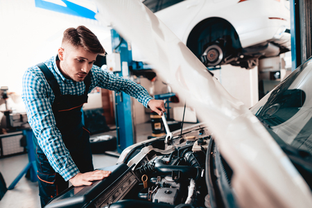 Young Auto Mechanic Repairs Car With A Wrench. Under The Hood. Professional Uniform. Confident Engineering Specialist Team. Service Station Concept. Automobile Diagnostic. Working In Garage.