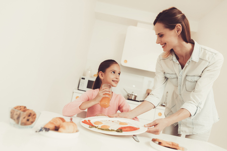 Mom Is Giving Daughter A Breakfast At The Kitchen. Happy Family Relationship Concept. Ready To Eat. Morning Nutrition. Kitchenware On Table. Knife And Fork. Plate With Meal. Healthy Food. Reklamní fotografie