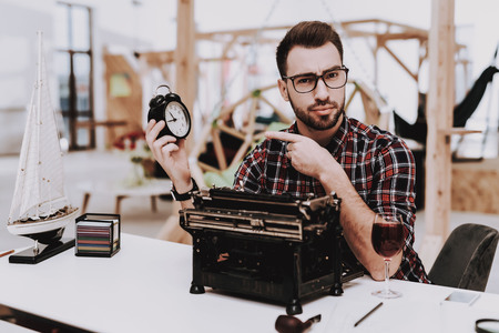 Alarm Clock. Old Typewriter. Pipe for Smoking. Young Male. Businessman. Working in Office. Creates Ideas. Eyeglasses. Workplace. Project. Sit. Brainstorm. Work. Office. Creative Worker. Inspiration.