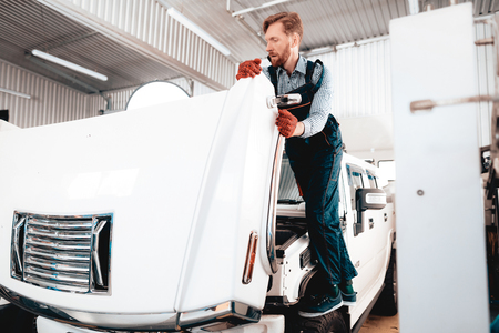 Red-haired Mechanic Stands On Wheel. Open Hood. Professional Uniform. Confident Engineering Specialist Stare. Protective Gloves. Working In The Garage. Young Repairman Posing Concept. Big SUV. Imagens