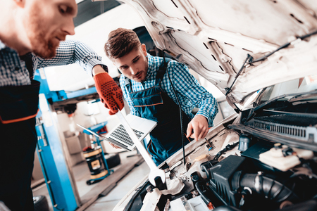 Young Auto Mechanic Repairs Car With A Wrench. Under The Hood. Professional Uniform. Using Laptop. Engineering Specialist Team. Service Station Concept. Automobile Diagnostic. Working In Garage.
