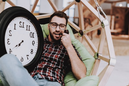 Big Watch. Hanging Chair. Clock. Eyeglasses. Young Male. Businessman. Working in Office. Creates Ideas. Eyeglasses. Workplace. Project. Sit. Brainstorm. Work. Office. Creative Worker. Inspiration. Banco de Imagens