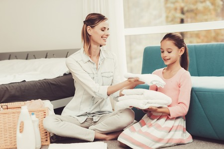 Daughter Helps The Mother With Household Chores. Bright Room. Clean Laundry. Young Helper. Holiday Leisure. Family Relationship Concept. Domestic Problems. White Towels. Parents Duty.