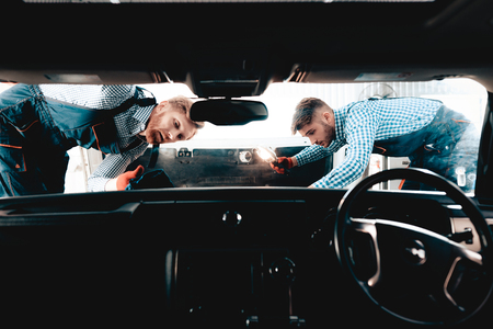 Two Auto Mechanics Are Looking Under The Hood. Front Seat View. Professional Uniform. Confident Engineering Specialist Team. Service Station Concept. Working Together In Garage. Details Repairing.