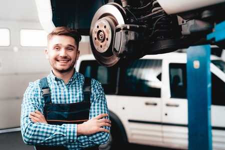 Young Mechanic Posing With Wrench In The Garage. Professional Uniform. Service Station Concept. Confident Engineer Stare. Detail Repairing. Under The Vehicle. Automobile Diagnostic.