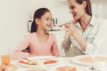 Mom With Daughter Are Having A Dinner At Kitchen. Family Relationship Concept. Having Fun During The Breakfast. Morning Nutrition. Feeding From Spoon. Happy Childhood Concept. Time To Lunch. Foto de archivo - 109389996