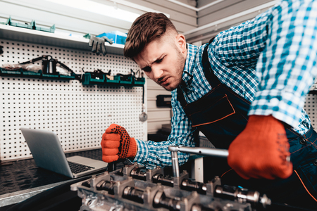 Young Auto Mechanic Twists A Nut. Service Station Concept. Wrench Using. Detail Reparing. Professional Uniform. Confident Engineering Specialist. Protective Gloves. Working In Garage.