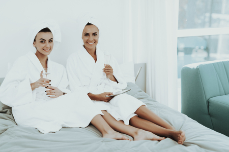 Girls In A Bathrobes Are Looking At Tablet Screen. Beautiful Shiny Smile. Sunny Day. Good Mood. Young And Attractive. Towel On Head. Good Mood. Drinking Champagne. Pre-wedding Care Concept. Stok Fotoğraf - 109456782