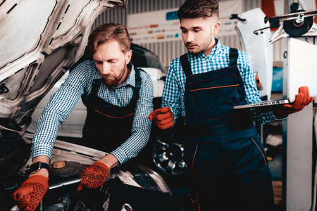 Two Auto Mechanics Work Together In Garage. Wrench Using. Laptop Screen. Under The Hood. Professional Uniform. Red Protective Gloves. Service Station Concept. Automobile Diagnostic. Banque d'images - 109390114