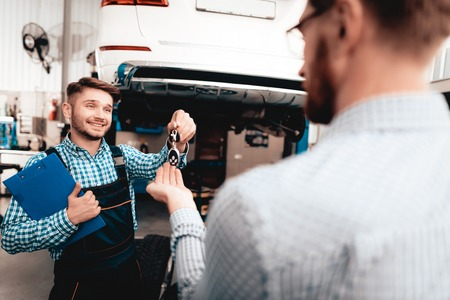 Auto Mechanic Gives Keys To The Car Owner In Garage. Trust Justify. Professional Uniform. Confident Engineer Stare. Repair Young Specialist. Service Station Concept. Machine Repairing.