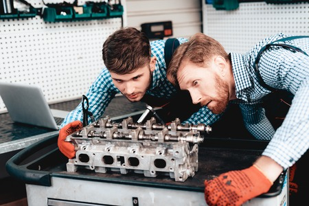 Two Auto Mechanics Are Checking Detail In Garage. Professional Uniform. Confident Engineering Specialist Stare. Protective Gloves. Working In The Garage. Young Repairman Posing Concept. Stockfoto - 109390149