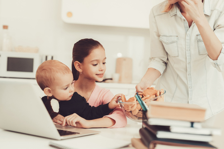 Young Girl Plays With Baby Brother On Kitchen. Happy Childhood Concept. Active Kids. Mom With Cookies Background. Family Holiday Leisure. Writing On The Laptop Keyboard. Parent's Duty. Banque d'images - 109390189