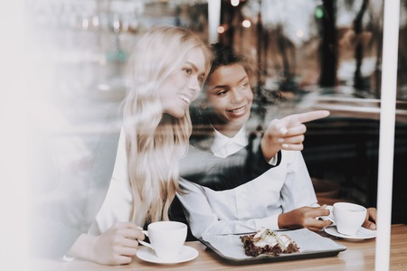 Cafe. Blond Girl. Mulatto. Sit. Drink Coffee. Window. Have Fun. Food in Plate. Food to Customers. Rest. Together. Joyful. Chin-chin. Leisure Time. Nightlife. Positive. Emotion. Clubbing. Guys.
