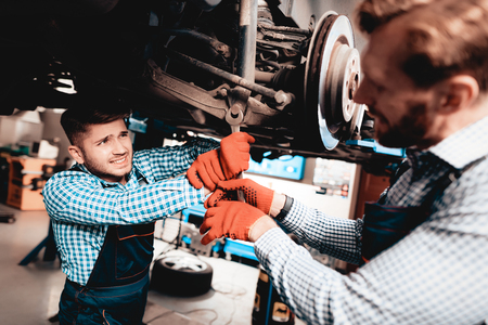 Young Mechanic Repairs Automotive Hub In Garage. Professional Uniform. Service Station Concept. Confident Engineer Stare. Detail Repairing. Under The Vehicle. Automobile Diagnostic. Join Forces. Фото со стока