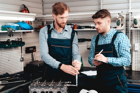 Two Auto Mechanics Work Together In Garage. Wrench Using. Colleagues Discussion. Information Sharing. Professional Uniform. Confident Engineering Specialist Team. Service Station Concept.