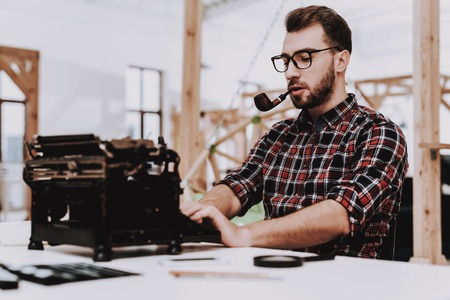 Pipe for Smoking. Old Typewriter. Hands. Young Male. Businessman. Working in Office. Creative Worker. Creates Ideas. Eyeglasses. Desk. Workplace. Project. Sit. Brainstorm. Work. Office. Inspiration.