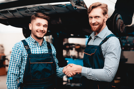 Two Young Smiling Auto Mechanics In The Garage. Handshake Concept. Professional Uniform. Service Station Concept. Confident Engineer Stare. Working Together. Under The Vehicle. Repairman Specialists. 写真素材 - 109390233