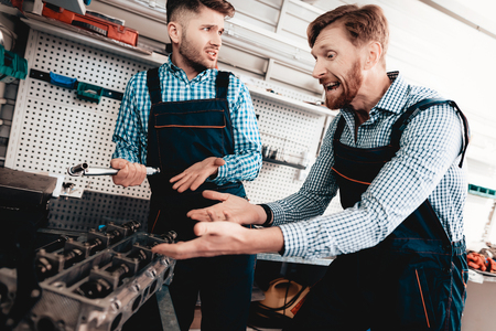 Two Mechanics Conversation In The Garage. Wrench Using. Arguing Colleagues. Information Sharing. Professional Uniform. Confident Engineering Specialist Team. Service Station Concept.