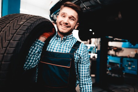 Young Smiling Mechanic Holds A Car Tire At Service Station. Professional Uniform. Confident Engineer Stare. Cheerful Repairman. Working In The Garage. Protective Gloves. Repairman Specialist. Stock Photo