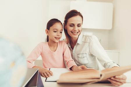 Mom Helps Daughter To Do Homework In The Kitchen. Family Relationship Concept. Educational Childhood. Studying At Home. Knowledge Receiving. Information Writing. Parents Duty. Working Together. Reklamní fotografie