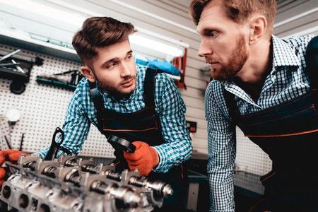 Two Auto Mechanics Are Checking Detail In Garage. Professional Uniform. Confident Engineering Specialist Stare. Protective Gloves. Working In The Garage. Young Repairman Posing Concept.