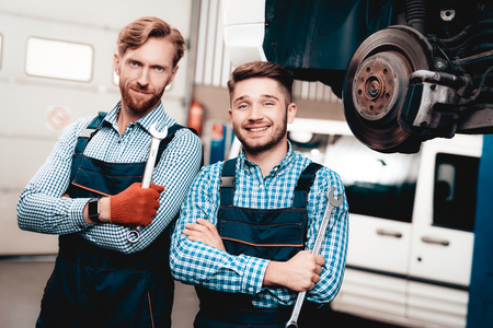 Two Automechanics Posing With Wrenches In Garage. Professional Uniform. Service Station Concept. Confident Engineer Stare. Detail Repairing. Under The Vehicle. Automobile Diagnostic.