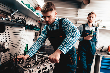 Young Auto Mechanic Repairs Detail In The Garage. Wrench Using Concept. Beer Drinking Background. Working On A Service Station. Professional Uniform. Confident Engineering Specialist.