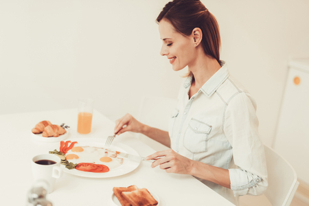 Woman Is Eating An Omelette. Breakfast Concept. Having A Breakfast In The Kitchen. Morning Nutrition Concept. Kitchenware On Table. Knife And Fork. Ready To Eat. Plate With Meal. Delicious Lunch.