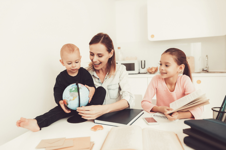Mom Helps Daughter To Do Homework In The Kitchen. Family Relationship Concept. Educational Childhood. Studying At Home. Knowledge Receiving. Hold A Baby. Play With Globe. Working Together.