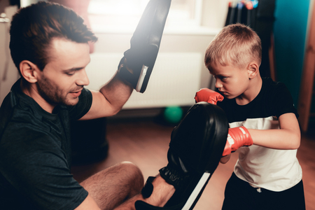 Father And Son Boxing Exercises Training In Gym. Parenthood Relationship. Sporty Family Concept. Active Lifestyle. Kid In Boxing Gloves. Holiday Leisure. Working Out Together. Fitness Day. 스톡 콘텐츠